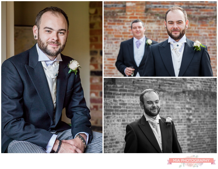 groom posing for his wedding photographer a bury court barn in hampshire